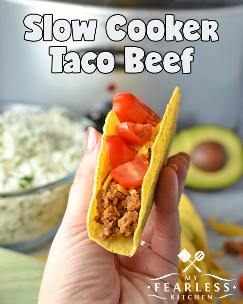 a hand holding a taco with cheese and tomatoes, with rice, avocado, and a slow cooker in the background
