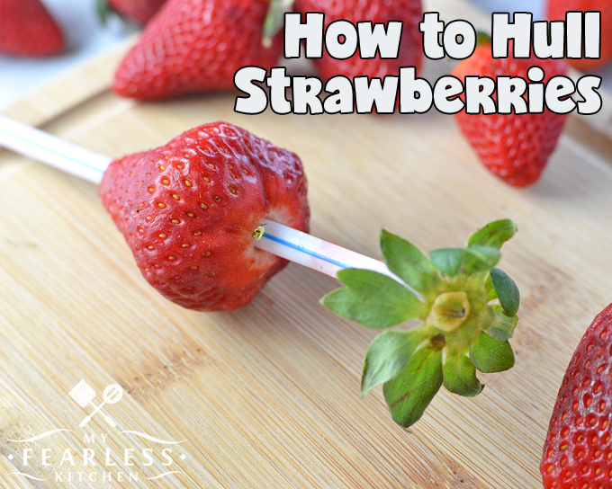 using a straw to take the hulls and green leaves off a ripe strawberry
