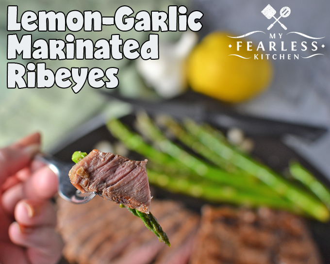 piece of lemon-garlic marinated steak on a fork with an asparagus spear