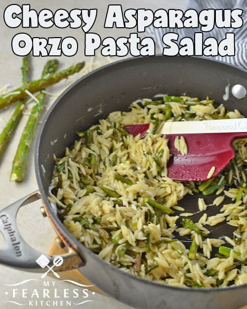 warm pasta salad with asparagus and melted parmesan cheese in a skillet