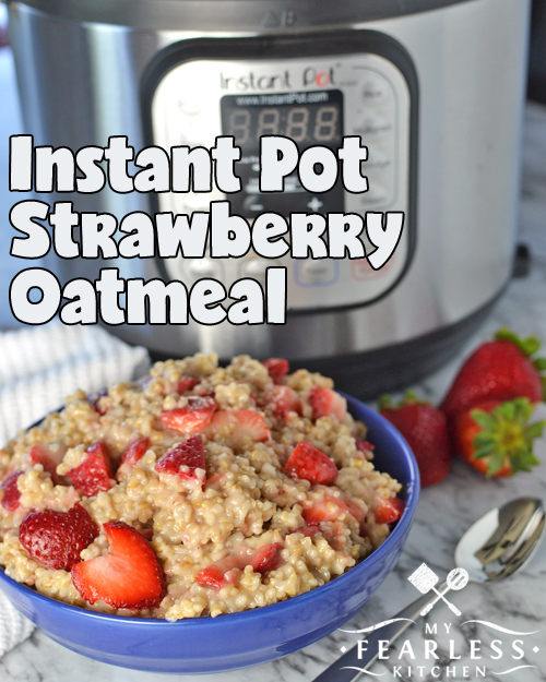 steel-cut strawberry oatmeal in a blue bowl with fresh strawberries and an Instant Pot in the background