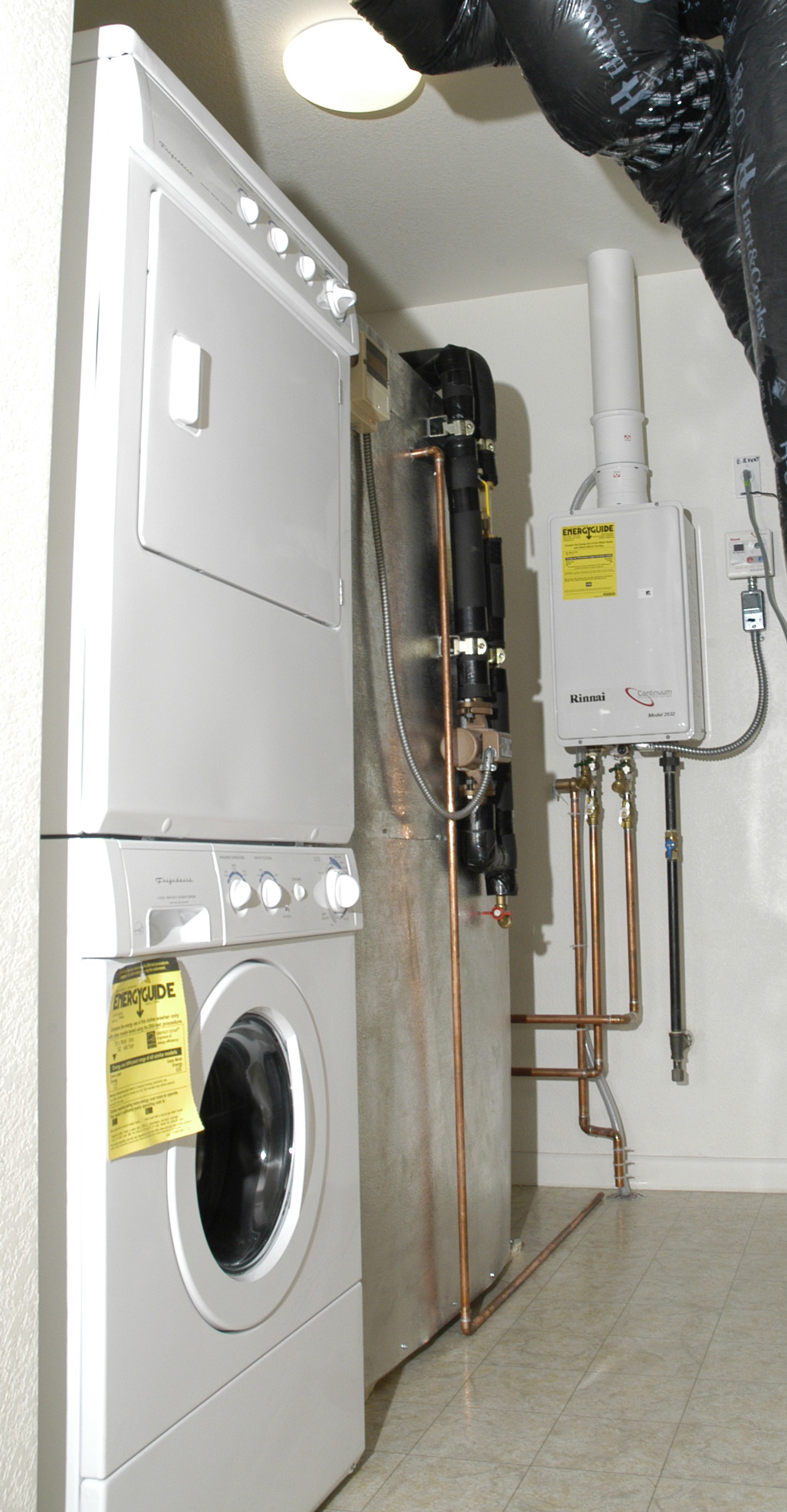 hight resolution of a whole house tankless gas water heater installed in a laundry room