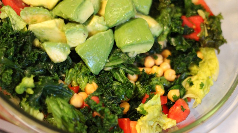 raw kale salad with avocado and tomato