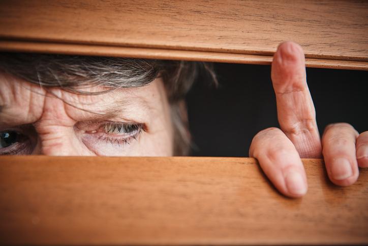 person with agoraphobia peeking out window