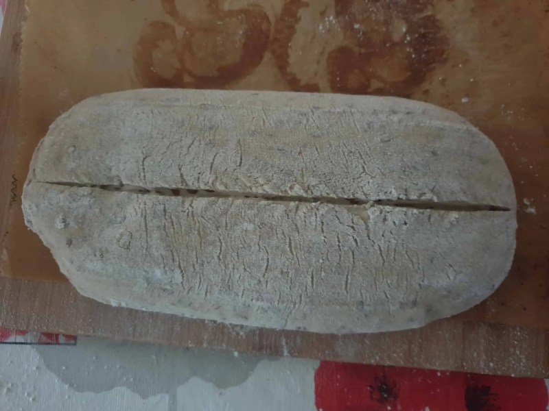 Scoring the dough for mixed bread with seeds