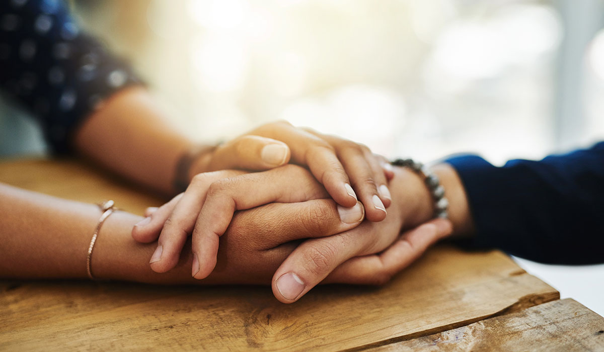 A closeup shot of two people holding hands