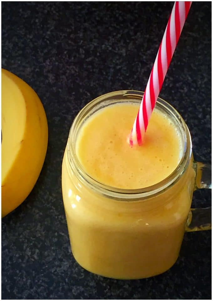 A jar of manago and banana smoothie with a banana next to it