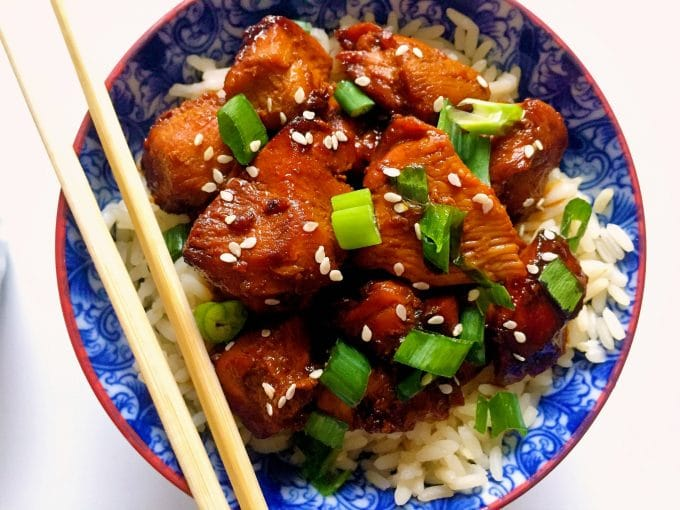 Overhead shot of a blue bowl of grilled teriyaki chicken with rice and wooden chopsticks on the side