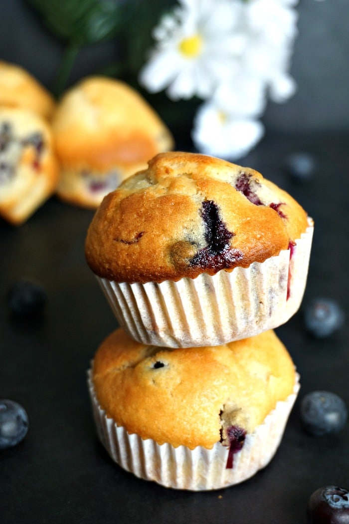 A stack of two fluffy blueberry muffins with blueberries scattered around them