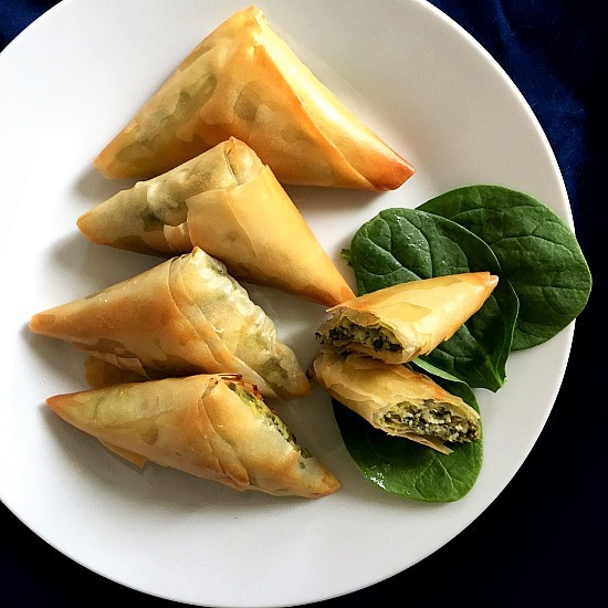 4 spanakopita triangles and one trinagle halved on a white plate and 3 fresh spinach leaves