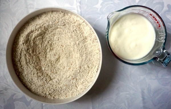 Overhead shot of a bowl of flour and a jug of buttermilk to make traditional Irish soda bread