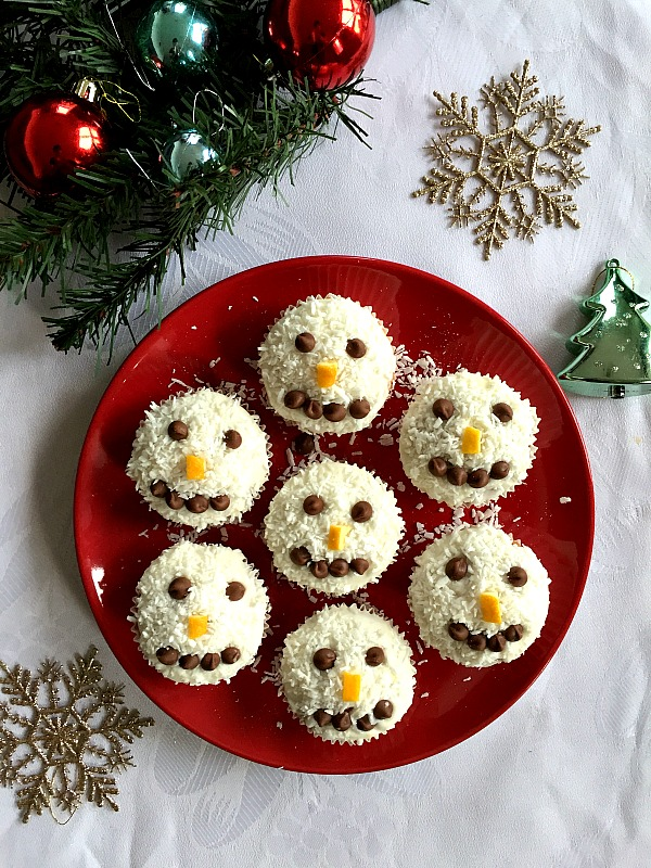7 snowman cupcakes on a red plate with Christmas decorations around