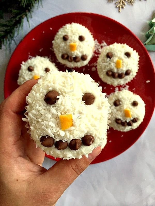 A snowman cupcake with other cupcakes on a red plate in the background