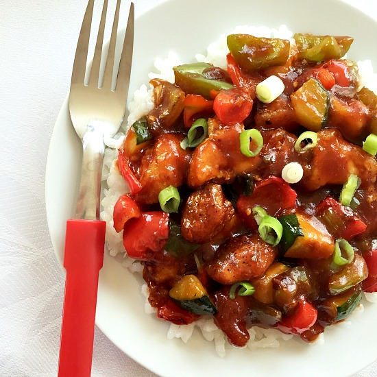 Overhead shot of sweet and sour chicken with vegetables with a fork on the edge of the plate