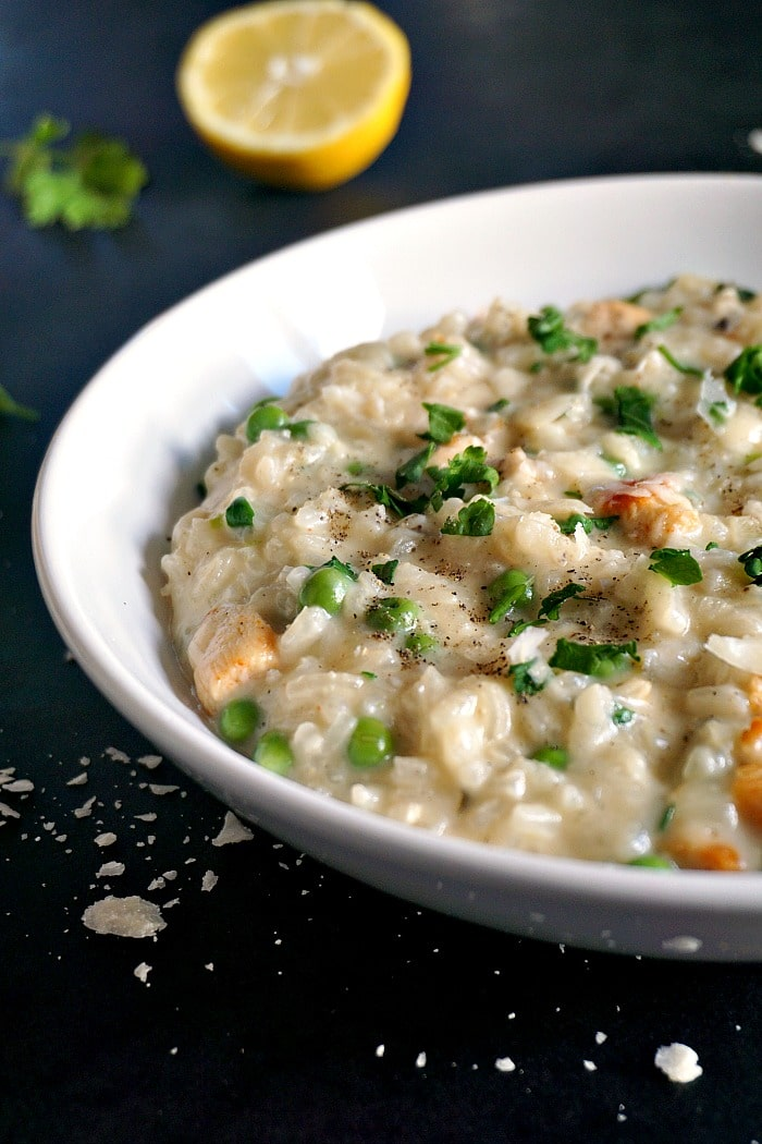 A white plate of Creamy chicken risotto with peas, a slice of lemon, parsley and grated cheese in the background