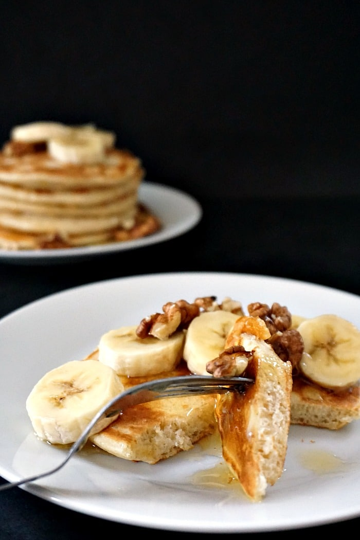 A white plate with a fork halving a fluffy American pancake which is topped with sliced bananas and wlanuts