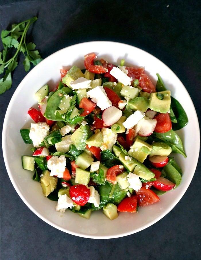 Overhead shot of a white plate of cucumber tomato avocado feta salad