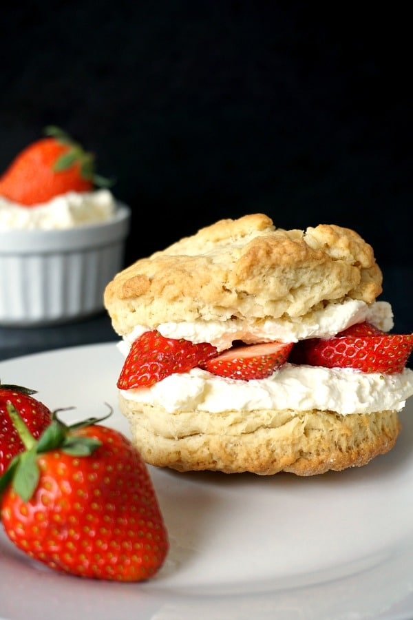 A strawberry and cream shortcake with 2 strawberries next to it