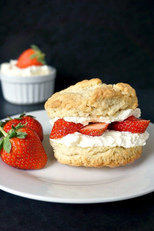 A white plate with a shortcake with 2 strawberries next to it and a white rameskin with cream and a strawberry in the background