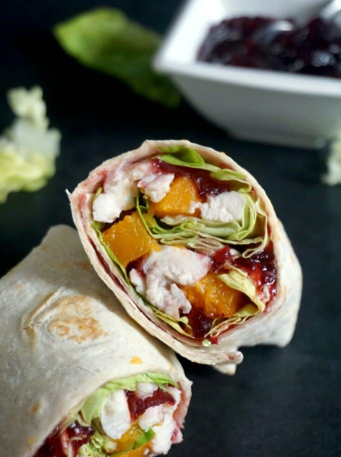 2 Healthy leftover turkey wraps with cranberry sauce with a small white bowl of cranberry sauce in the background