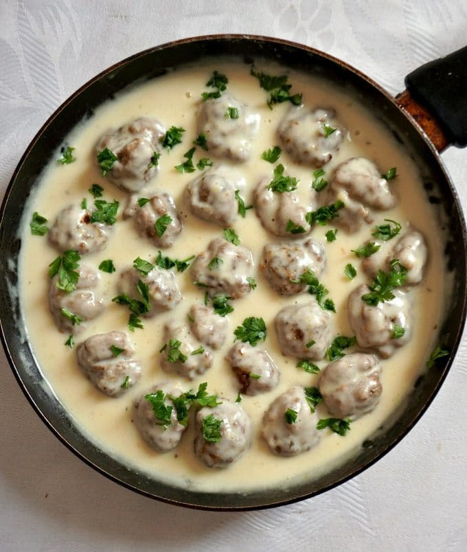 A black pan of Healthy Swedish meatballs in sauce garnised with choppped parsley