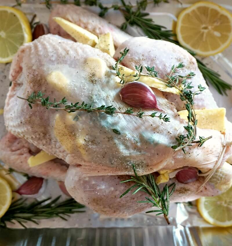 Overhead photo of a whole chicken in a roasting tray with herbs and seasoning.