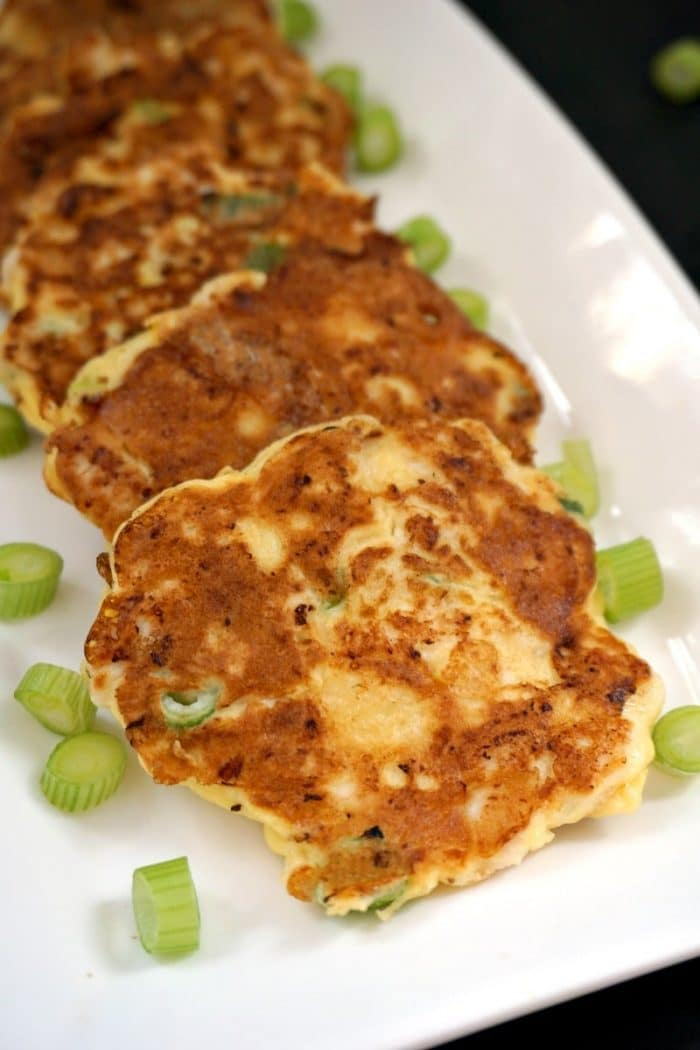 4 chicken fritters on a white plate with chopped green onions scattered around