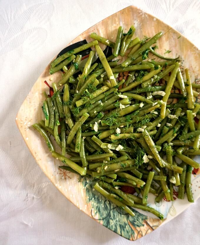 Overhead shot of a plate of garlicky green greens on a white table cloth