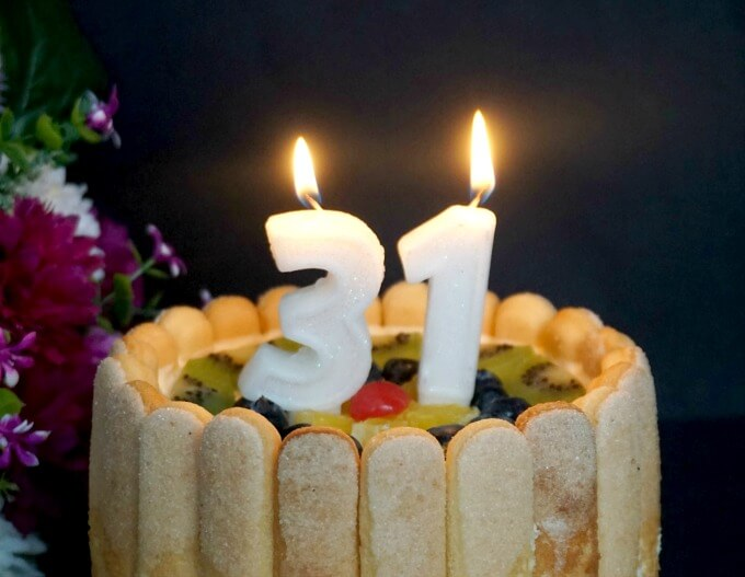A Charlotte Cake with 2 candles lit to celebrate a 31st birthday