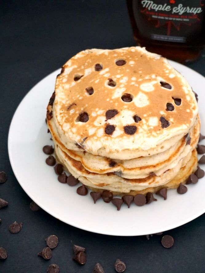A stack of banana chocolate chip pancakes on a white plate with chocolate chips around the pancakes