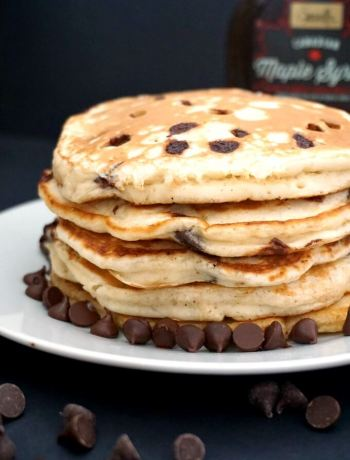 A stack of 5 banana chocolate chip pancakes on a white plate with chocolate chips around the pancakes