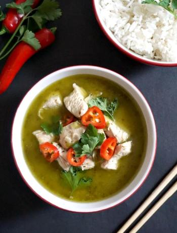 Overhead shot of a bowl of Thai Green Chicken Curry, a bowl of rice, chopsticks, 2 red chilli peppers and coriander leaves on the side