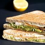 2 halves of grilled chicken sandwich with avocado and half a lemon in the background