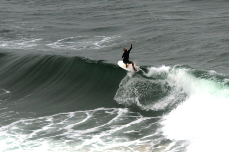 Endlich eine passende Welle: ein Surfer in Byron Bay