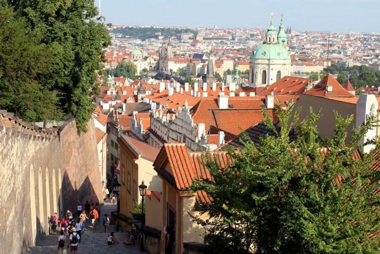 Unterhalb der Prager Burg geht es mit tollen Ausblicken auf die Altstadt jenseits der Karlsbrücke Richtung Moldau