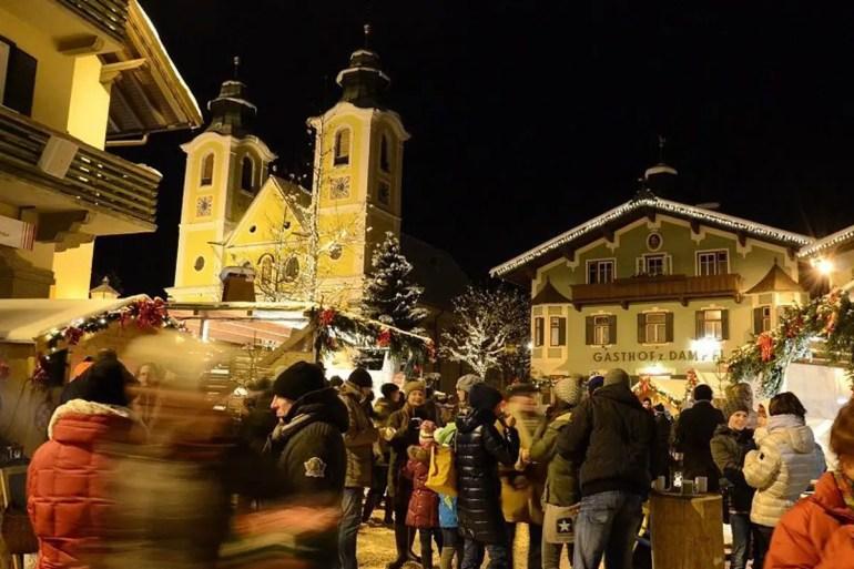 Im Dezember wird der Hauptplatz mit der Pfarrkirche zur romantischen Weihnachtsmarktkulisse (Credit: Region St. Johann in Tirol / Markus Rudolf)