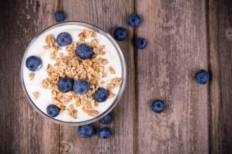 Yogurt with granola and fresh blueberries, in glass bowl over ol