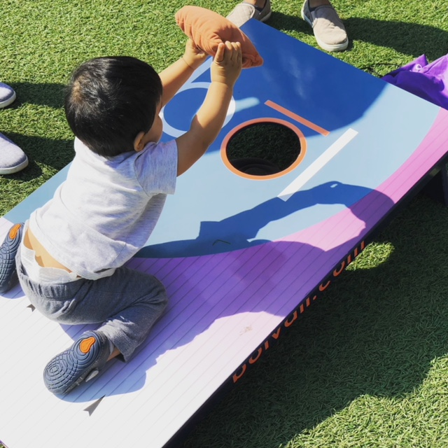 Baby playing cornhole
