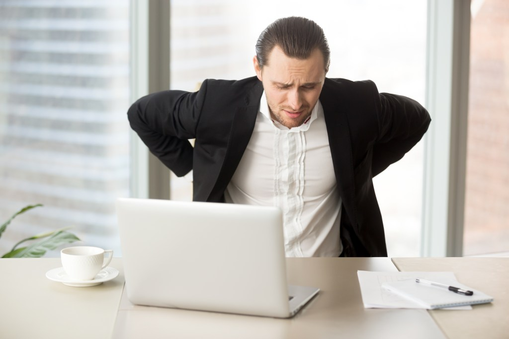 Businessman suffering from backache at workplace