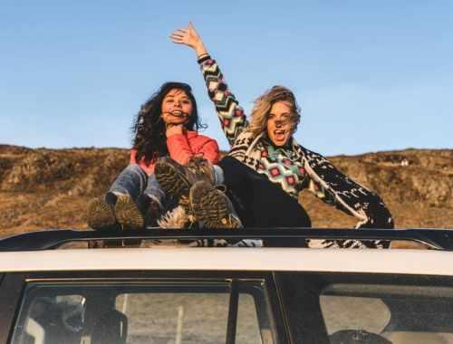 jeunes voyageuses sur le toit d'une voiture pour partir en vacances