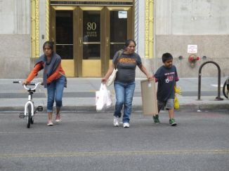 Latino family traverses West 14th Street.