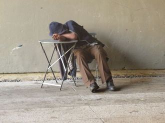 Homeless man naps as tourists pass.