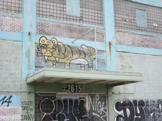 Graffiti lion perched on derilict factory.
