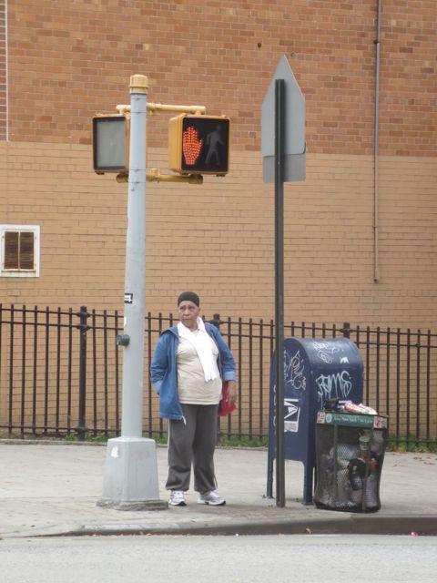 Lady crosses Kingsbridge Road.