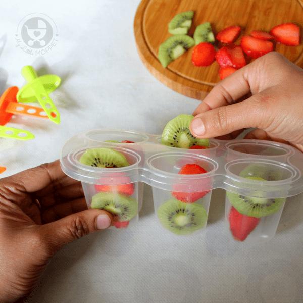 Arrange the fruit slices into popsicle moulds