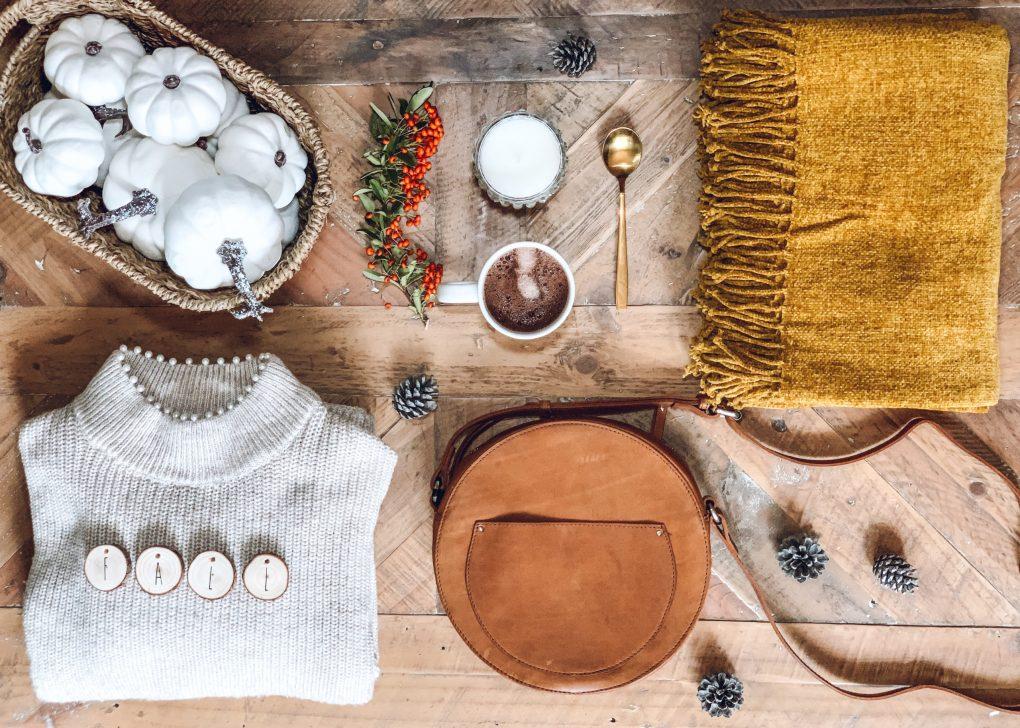 Table avec un plaid jaune moutarde, un sac camel, un tasse de chocolat chaud, un pull beige, une bougie, des courges blanches et des pommes de pin