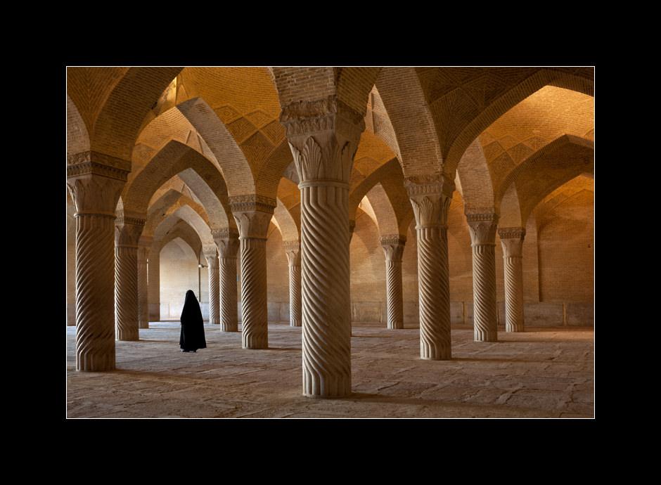 A traditionally dressed woman in the night prayer hall (Shabestan) of Masjed-e Vakil mosque, Shiraz, Iran.