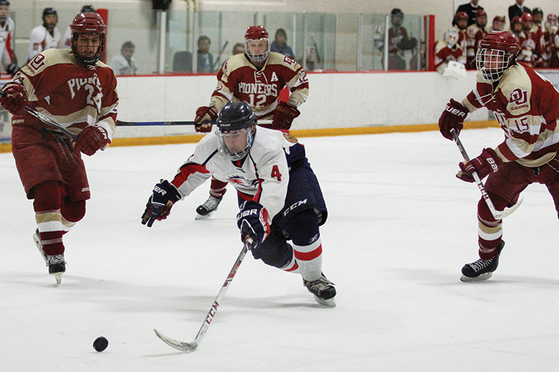 MSU's Ryan Gauthier (4) drives through DU's Cole Simpson (24), Tylar Novi (12) and Brian Desmond (15). The Roadrunners beat the Pioneers 6-4 at The Edge Ice Arena in Littleton on Friday, Oct. 16, 2015. Photo by Tom Skelley • tskelly@msudenver.edu