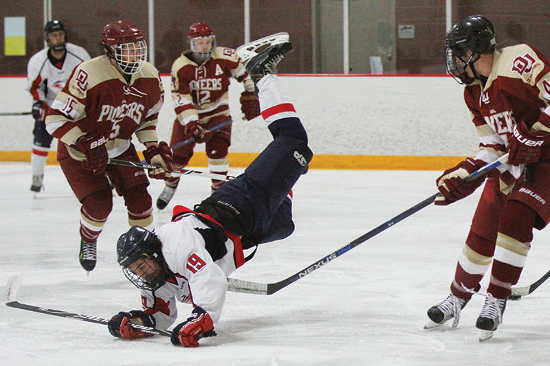 Metropolitan State forward Shane Doerfler (19) gets tripped up by DU defenseman David Kaplan (4) as Brian Desmond (15) and Tylar Novi (12) look on. The Roadrunners beat the Pioneers 6-4 at The Edge Ice Arena in Littleton on Friday, Oct. 16, 2015. Photo by Tom Skelley • tskelly@msudenver.edu