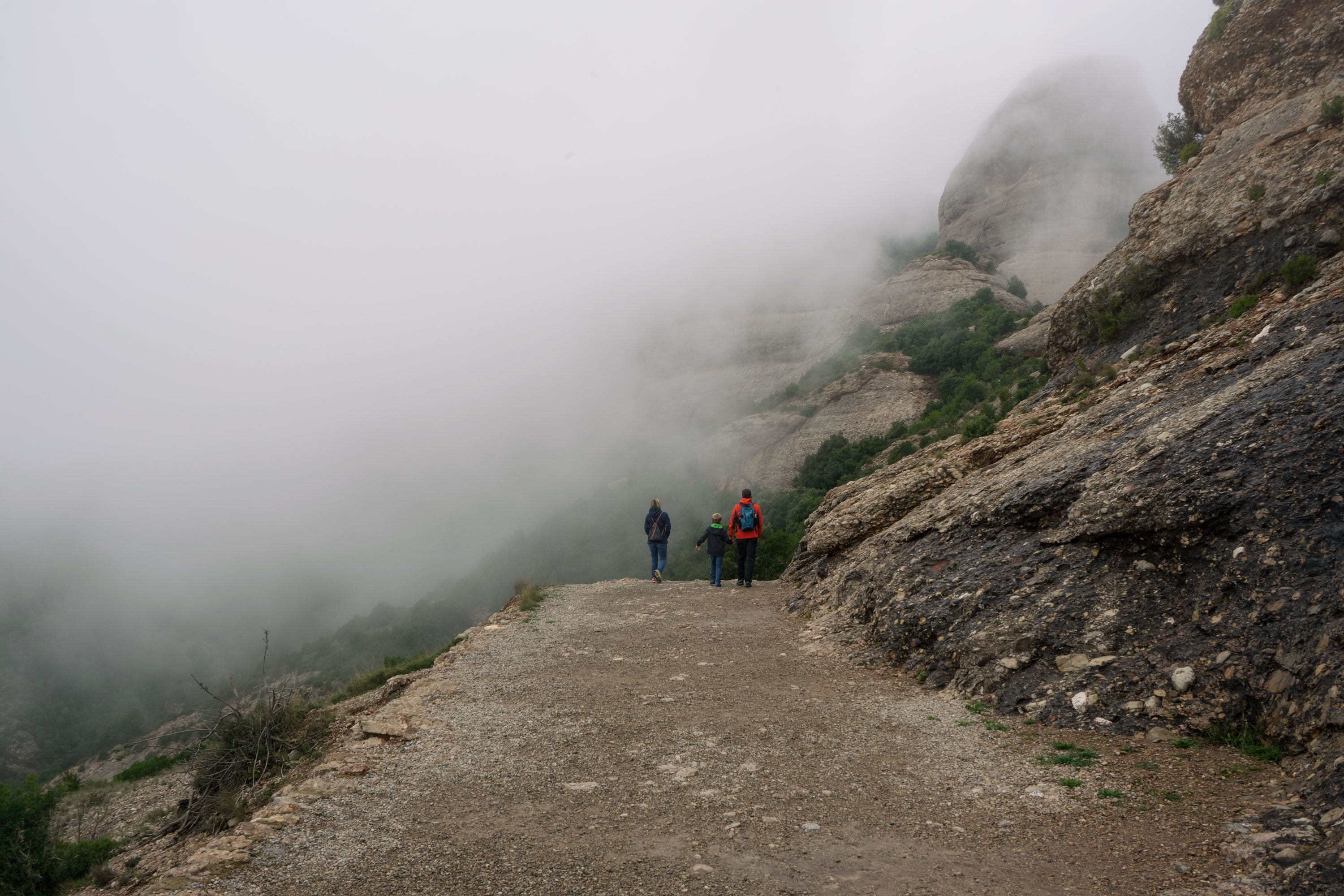 Family hiking the foggy Montserrat